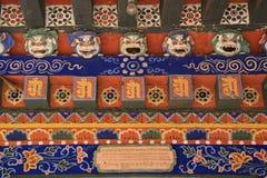 De gebeeldhouwde maskers van leeuw en de geschilderde bloemenpatronen verfraaien de poort van een boeddhistische tempel in Gangte Royalty-vrije Stock Foto
