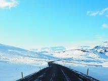 De gebogen weg van het de winterasfalt met berg aan de kant van de weg Stock Fotografie