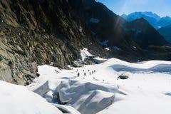 De gebonden klimmers die berg met sneeuwgebied beklimmen bonden met een kabel met ijsassen en helmen stock fotografie