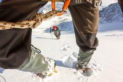 De gebonden klimmers die berg met sneeuwgebied beklimmen bonden met een kabel met van ijsassen en helmen eerste persoon Royalty-vrije Stock Foto's