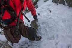 De gebonden klimmers die berg met sneeuwgebied beklimmen bonden met een kabel met van ijsassen en helmen eerste persoon Stock Foto
