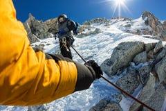 De gebonden klimmers die berg met sneeuwgebied beklimmen bonden met een kabel met van ijsassen en helmen eerste persoon Royalty-vrije Stock Foto