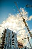 De gebouwen, de hemel en de kranen van het glas stock afbeeldingen