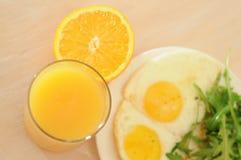 De gebraden eieren met arugula, jus d'orange, croissant, continentaal ontbijtconcept stock fotografie