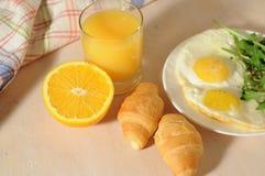 De gebraden eieren met arugula, jus d'orange, croissant, continentaal ontbijtconcept royalty-vrije stock fotografie