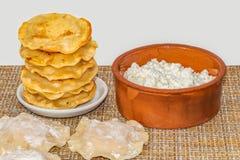 De gebraden gele tortilla's met kwark liggen als een piramide op een kleine witte plaat en een klei bruine kom met royalty-vrije stock foto