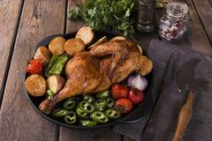 De gebraden kippenhelft met aardappels en tomaten in de pan Stock Afbeeldingen