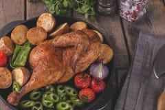 De gebraden kippenhelft met aardappels en tomaten in de pan Royalty-vrije Stock Foto