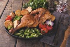 De gebraden kippenhelft met aardappels en tomaten in de pan Royalty-vrije Stock Afbeelding