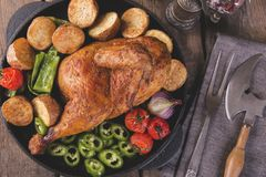 De gebraden kippenhelft met aardappels en tomaten in de pan Royalty-vrije Stock Afbeeldingen