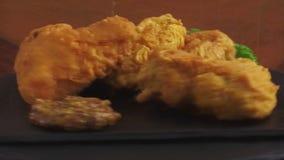 De gebraden kippenvleugels in beslag met saus op een steenoppervlakte roteren stock videobeelden