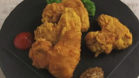 De gebraden kippenvleugels in beslag met saus op een steenoppervlakte roteren stock footage