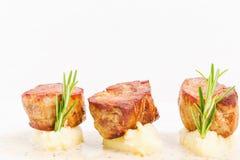 De gebraden medaillons van het varkensvleeshaasbiefstuk op fijngestampte aardappels Stock Afbeeldingen
