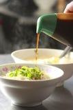 De gebraden noedel voegt zwarte rijstazijn toe stock fotografie