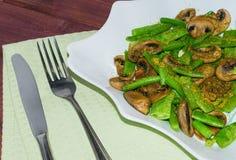 De gebraden paddestoelen met verse groene erwten dienden op lichtgroene tafelkleed gestemde selectieve nadruk Stock Fotografie