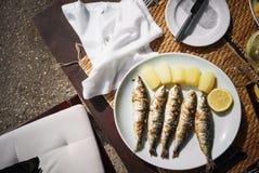 De gebraden smakelijke makreel, een plak van citroen en de gele aardappels liggen op een witte plaat, die zich op een houten lijs stock foto