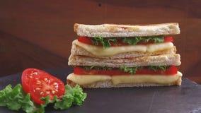 De gebraden toost met kaas en de tomaat op een steenoppervlakte roteren stock videobeelden