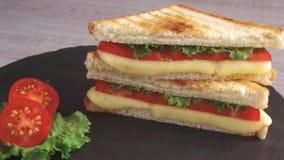 De gebraden toost met kaas en de tomaat op een steenoppervlakte roteren stock video