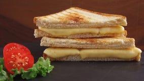 De gebraden toost met kaas op een steenoppervlakte roteert stock videobeelden