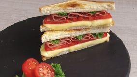 De gebraden toost met de salami van de kaastomaat op een steenoppervlakte roteert stock video