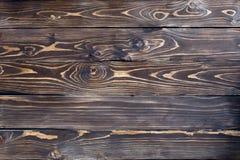 De gebrande bruine houten geschilderde niet achtergrond van de muurtextuur Stock Afbeelding