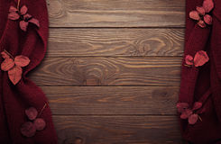 De gebreide sjaal van de kleur van Bourgondië met de herfstbladeren op dark streeft na Stock Afbeelding