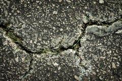 De gebreken en de tekorten geven aan zwakheid door gebarsten bestrating wordt getoond die Onvolmaaktheden en ruw asfalt Rots royalty-vrije stock afbeeldingen
