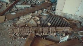 De gebroken delen van een piano liggen in een geruïneerd gebouw in het midden van huisvuil stock videobeelden