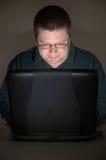De gebruiker van de computer in verdonkerde ruimte Stock Fotografie