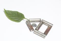 De gebruikte batterijen liggen in de vorm van een huis Boven hen is een sappig groen blad stock afbeeldingen