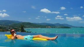 De gebruinde mens op matras in zwembad het drinken drank van metaal kan stock video