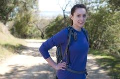 De gecentreerde wandelaarvrouw in blauw lang kokeroverhemd bekijkt camera Stock Afbeeldingen