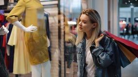 De gecharmeerde jonge blondevrouw loopt langs een showvenster met zakken in het winkelcomplex stock videobeelden