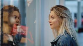 De gecharmeerde jonge tribunes van de blondevrouw vóór een showvenster in het winkelcomplex stock videobeelden