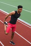 De geconcentreerde Afrikaanse atletenmens maakt uitrekkende oefeningen Royalty-vrije Stock Foto