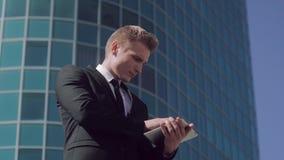 De geconcentreerde bedrijfsmens werkt in openlucht aan zijn tablet wanneer hij een prettige massage ontvangt stock video