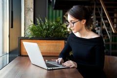 De geconcentreerde bedrijfsvrouw zit op koffie die aan laptop werken stock foto's