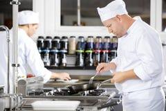 De geconcentreerde chef-koks maakt voedsel in professionele keuken royalty-vrije stock foto