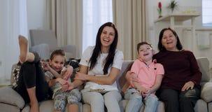 De geconcentreerde en grappige familieoma met haar mooie dochter en kleinkinderen let op een komediefilm op TV zij stock video
