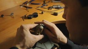 De geconcentreerde jonge juweelmeester bevestigt de halfedelsteen in de kroon op de langzame motie van de metaalring stock video