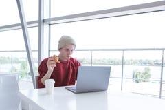 De geconcentreerde jonge zakenman die toevallige kleding dragen werkt aan laptop in een koffie en eet een sandwich stock foto