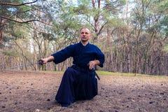 De geconcentreerde mens met een zwaard, katana oefent vechtsporten uit Stock Fotografie
