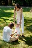 De geconcentreerde ouders onderwijzen hun kleine dochter die witte kleding dragen hoe te om haar eerste stappen op het gazon te m stock foto