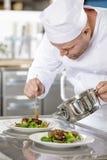 De geconcentreerde professionele chef-kok bereidt vleesschotel bij restaurant voor Royalty-vrije Stock Afbeeldingen