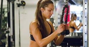 De geconcentreerde vrouw spieren die van de opleidingstriceps kabelmachine in gymnastiek trekken stock video