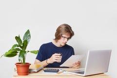 De geconcentreerde zakenman in eyewear examens dicht stuk van document, dranken meeneemkoffie, overzichtenfinanciën, zit voor ope Stock Fotografie