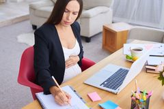De geconcentreerde zwangere hand van de onderneemsterholding op buik tijdens het werk royalty-vrije stock afbeelding