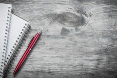 De gecontroleerde pen van notitieboekjesbiro op het houten concept van het raadsonderwijs royalty-vrije stock foto's