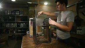 De gedemonteerde koffiemachine, de kerel` s hand maakt de oppervlakte van het koffiestof schoon, langzame motie stock video