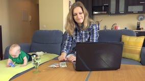 De gedeprimeerd computer van het vrouwenwerk en tellingsgeld De gelukkige Jongen van de Baby 4K stock footage
